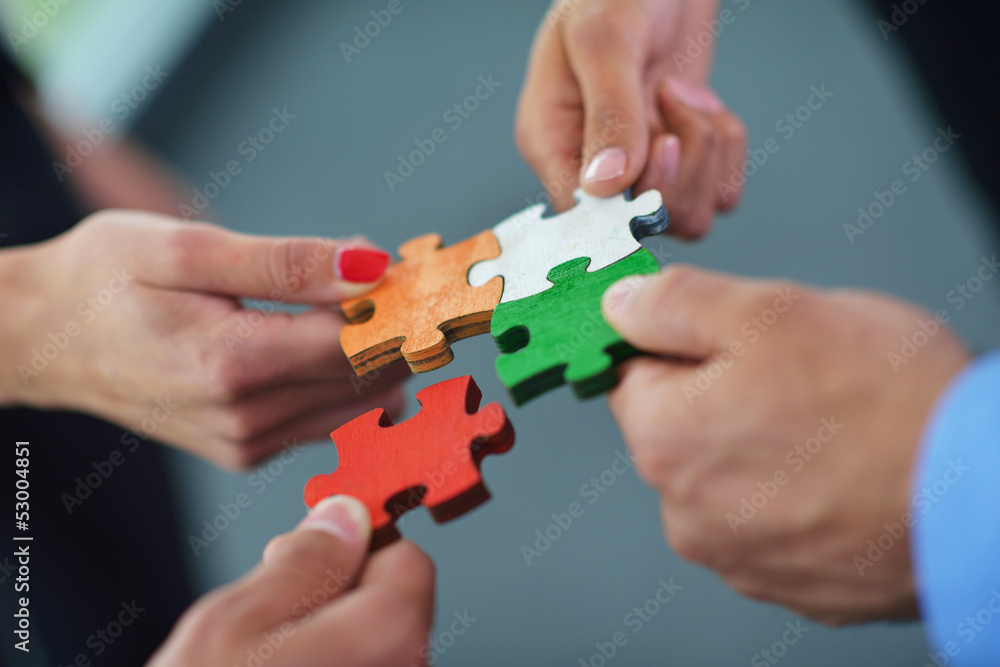 Fototapeta Group of business people assembling jigsaw puzzle