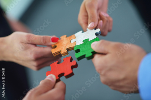 Obraz Group of business people assembling jigsaw puzzle - fototapety do salonu