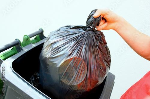jeter son sac poubelle noir dans un container Canvas Print