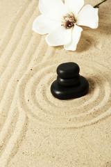Fototapeta na wymiar Zen garden with raked sand and round stones close up