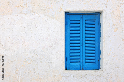White house facade with blue shutters in Pyrgos