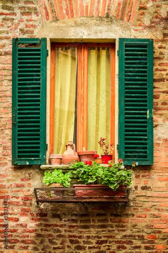 okno-w-starym-domu-ozdobione-doniczki-i-kwiaty