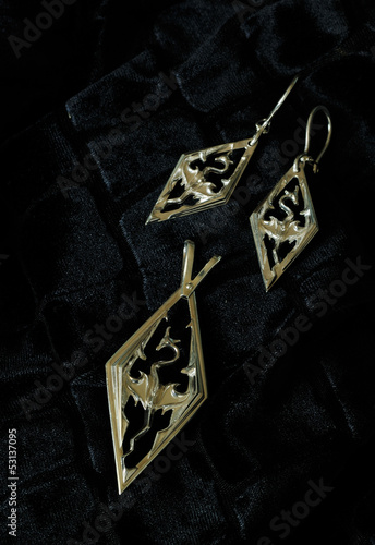 Photo  silver earrings and pendent with the image of a dragon on black
