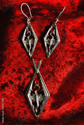 Photo  silver earrings and pendent with the image of a dragon on red