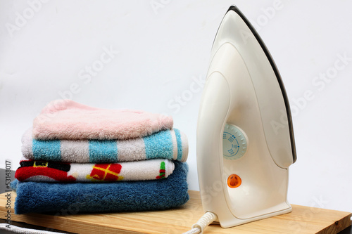 Fotografie, Obraz  Pile of colorful clothes and electric iron on white background