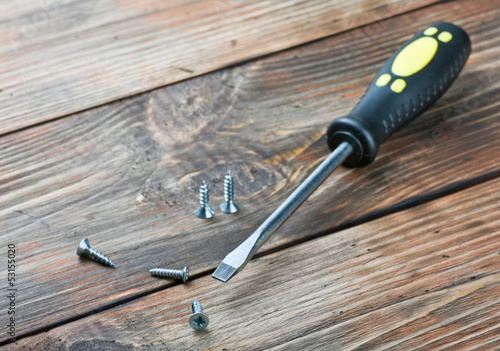 Foto screwdriver and screws on a wooden table