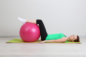 Fototapeta Portrait of beautiful young woman exercises with gym ball