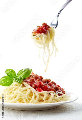 Spaghetti bolognese and green basil leaf on white plate Fototapeta