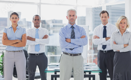 Fotomural  Team of business people standing with arms folded