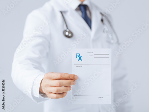 Photo  male doctor holding rx paper in hand