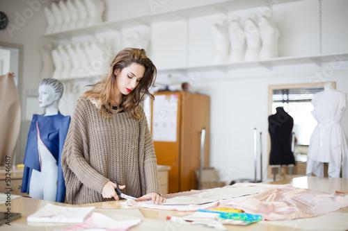Valokuvatapetti Fashion designer cutting fabric textile in a studio