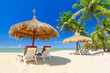 Tropical beach scenery with parasol and deck chairs in Thailand