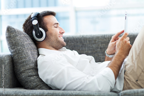 Fotografia  Man on sofa with headphones and digital tablet