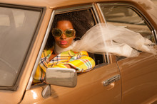 Vintage 70s Fashion Afro Woman With Sunglasses Driving In Brown