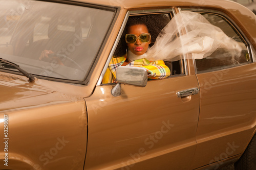 Vintage 70s fashion afro woman with sunglasses driving in brown Wallpaper Mural