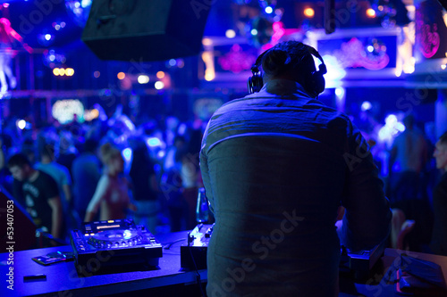Fotografía  DJ turns the records at the club under the blue light