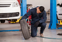 Young Mechanic Inspecting A Car Tire At An Auto Shop