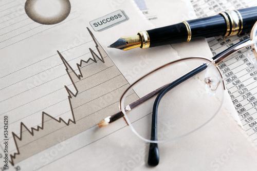 Fotografía  fondo de finanzas y economia.Estadisticas,graficos y gafas