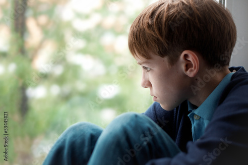 Fotografie, Obraz  Sad teenager sitting on window