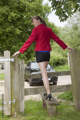Fotografie, Obraz  Woman stepping over a stile