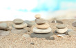 Towers of sea stones on sand on bright background