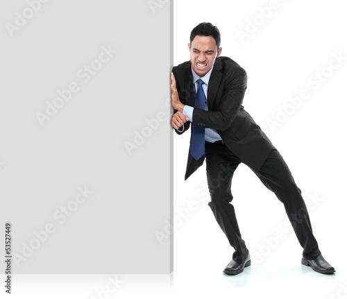 Cuadros en Lienzo Young businessman pushing a blank board