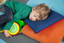 Boy Sleeping With Toy In Kinde...
