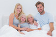Portrait of a cheerful family in bed