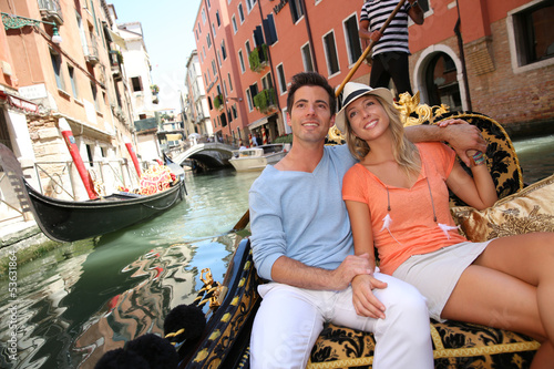 Poster Gondoles Couple in Venice having a Gondola ride on the canal