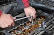 Mechanic fixing spark plug to car engine, ratchet, cam