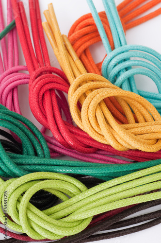 Fotografía  Shoelaces of different colors, knotted, isolated on white
