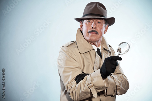 Retro detective man with mustache and hat. Holding magnifying gl Canvas Print