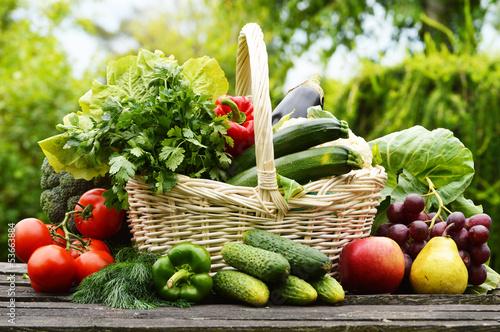 Staande foto Groenten Fresh organic vegetables in wicker basket in the garden