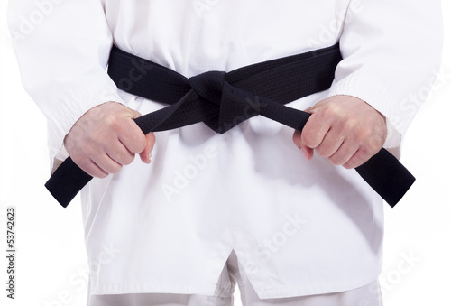 Foto op Plexiglas Vechtsport Martial arts man tying his black belt, isolated on white