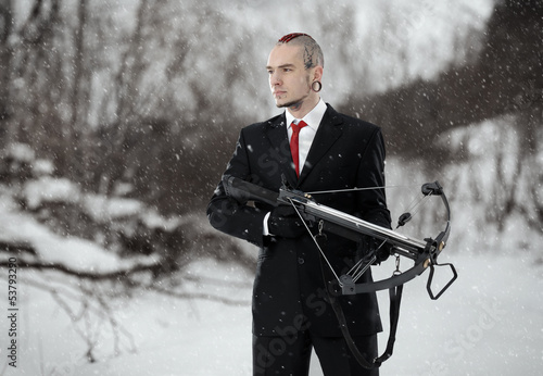 Tableau sur Toile Hitman with a crossbow in an outdoor setting.  Walking Dead.