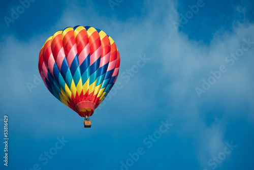Tuinposter Ballon Brightly colored hot air balloon with a sky blue background