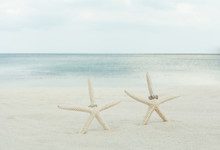 Wedding Rings With Starfish On A Sandy Beach.