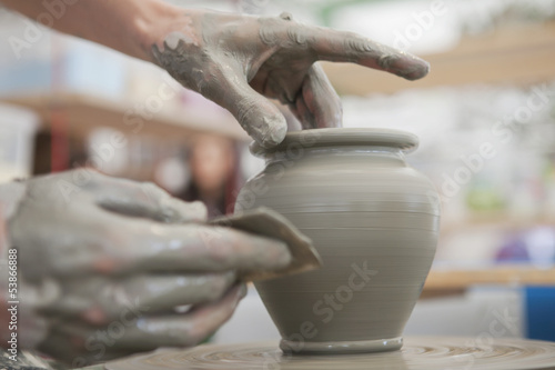Fotografie, Obraz  Hands Making Pottery On A Wheel