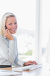 Blonde businesswoman on the phone smiling at camera