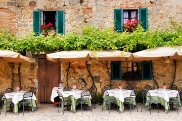 FototapetaCafe tables and chairs outside a stone building in Tuscany