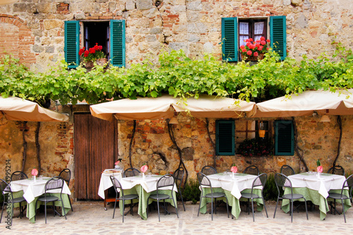 Poster Toscane Cafe tables and chairs outside a stone building in Tuscany