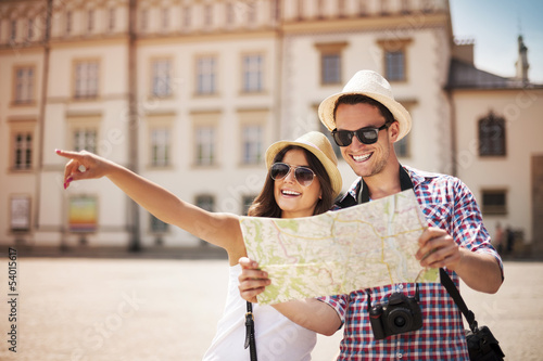 Foto  Happy tourists sightseeing city with map