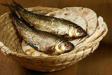 Loaves Of Bread And Two Fishes In A Basket.
