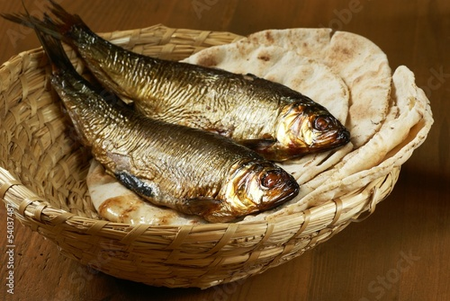 Poster de jardin Poisson Loaves of bread and two fishes in a basket.
