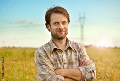Fotografía  Happy farmer standing in front of his fields