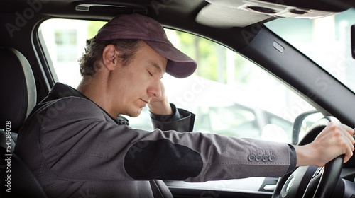 Foto  Bored man at the wheel of his car sleeping