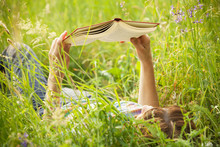 Girl Reading A Book Lying In The Tall Grass