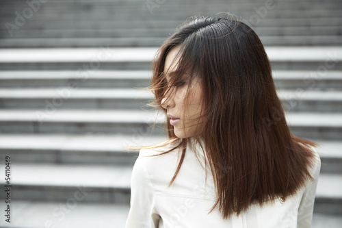 Fényképezés  Wind blowing hair over Chinese womans face