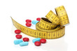 Measuring tape and medicine pills. Dieting concept