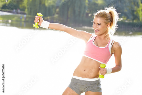 Fotografie, Obraz  fitness instructor exercising with small weights in city  park